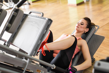 Fit young woman doing leg presses in the gym.