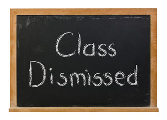 Class Dismissed written in white chalk on a black chalkboard isolated on white