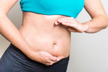 Junge Frau formt mit Händen Kreis vor Bauch