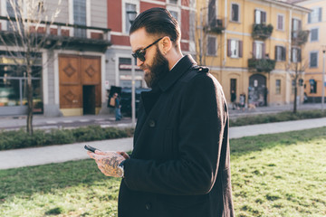 Young bearded business man outdoor using smart phone