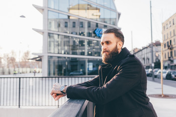 Young handsome caucasian bearded businessman looking over
