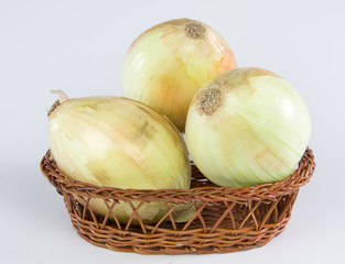onions in a bamboo basket isolated on white background