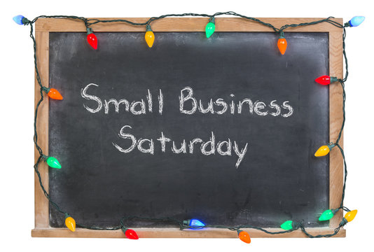 Small Business Saturday written in white chalk on a black chalkboard surrounded with festive colorful lights 