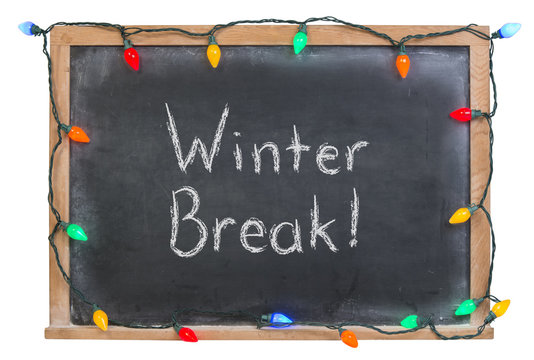 Winter break written in white chalk on a black chalkboard surrounded with festive colorful lights  isolated on white
