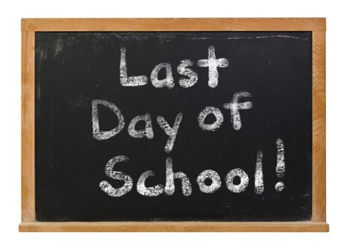 Last day of school written in white chalk on a black chalkboard isolated on white