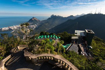 View of Tijuca forest mountains from the Corcovado Mountain, with green umbrellas below, and a staircase to Christ the Redeemer statue