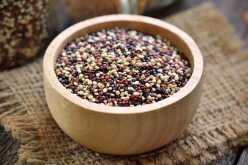 Quinoa seeds in bowl on wood