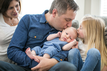 Family sitting on sofa, father and young girl kissing baby boy