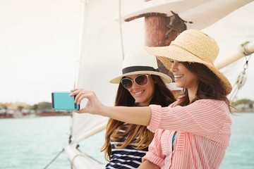 Two women on sailing boat, taking selfie, using smartphone