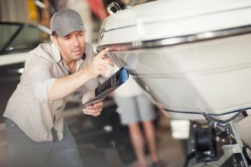 Man checking bodywork on boat in repair workshop