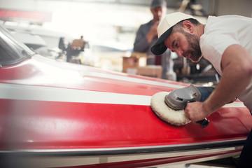 Man polishing boat in repair workshop