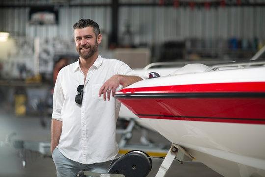 Portrait of man leaning against boat in repair workshop