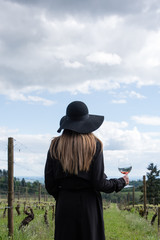 Woman standing in vineyard, holding glass of wine, rear view