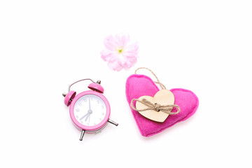 Spring composition of sakura flower, pink alarm clock and heart