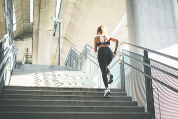 Young female athlete running on stairs