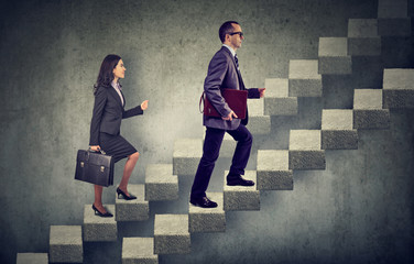 business woman and man with briefcase stepping up a stairway career ladder