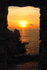 sunrise sunset over sea framed by window with stone steps leading to ocean