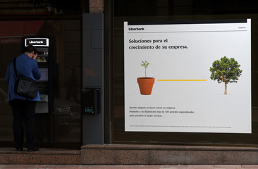 A man uses a cash dispenser at a branch of Spain's Liberbank in Oviedo
