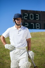 Confident cricket player with bat at field