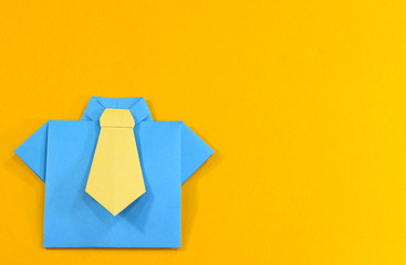 Father's day celebration. Origami shirt and tie on yellow background.