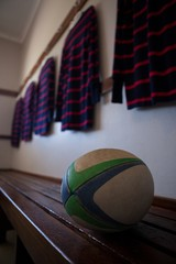 Rugby ball on bench against t-shirts