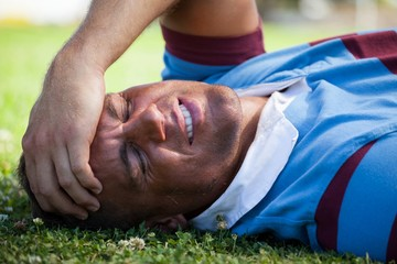 Injured rugby player with eyes closed lying on field