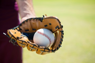 Cropped image of baseball pitcher holding ball on glove