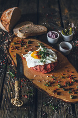 beef tatar with fried egg on wooden board
