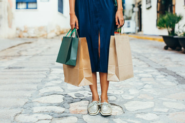 Closeup of a woman holding shopping bags on the street