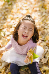 Young girl playing leaf in autumn wood