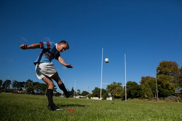 Rugby player kicking ball for goal against clear blue sky