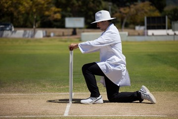 Full length of umpire putting bails on stumps