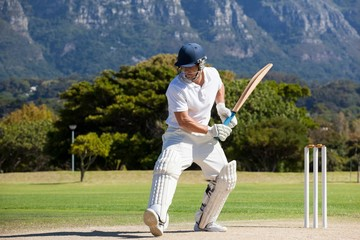 Full length of cricket player playing on field