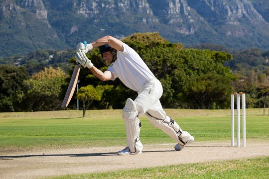 Full length of cricketer playing on field