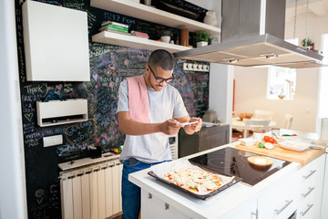 Man taking a photo with his phone to the handmade pizza at home