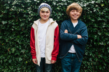 Two cool tween boys stand together smiling