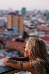 young blonde asian model looks out at city skyline