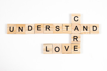 love,care and understand word written on wood block