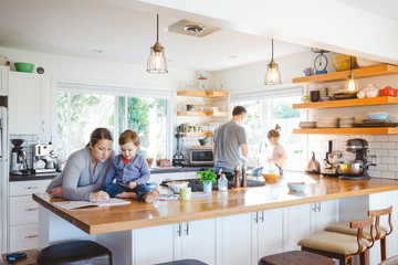Cool, young family spending time together in bright, modern kitchen