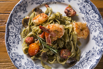 Basil fettuccine with seafood, shrimp and tomato