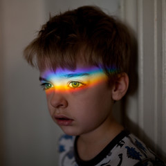 Young boy with rainbow across his eyes