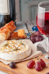 Brie cheese with rosemary and honey sealed in the oven, skewers with croutons and fresh grapes and a glass of red wine on a white wooden table. Close up