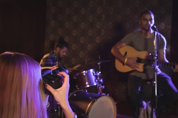 Woman photographing singer and musicians in nightclub