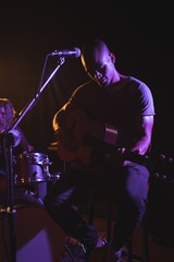 Male singer performing with guitar in nightclub