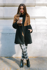 Beautiful woman with a coffee to go