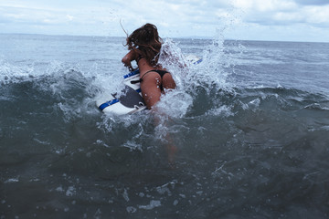 A sexy young woman jumps into the surf on her surfboard