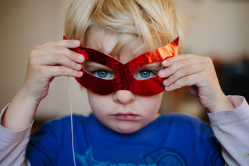 Boy with blue eyes looks through red paper mask