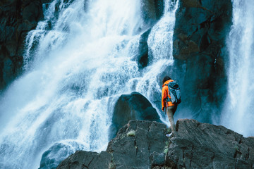 Hiker with backpack standing in front of a scenic waterfall
