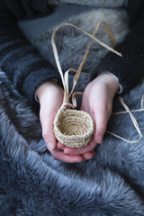 Girls hands holding tiny raffia basket - vertical