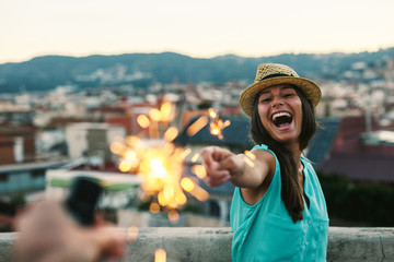Happy young woman holding sparklers standing on a rooftop at sunset